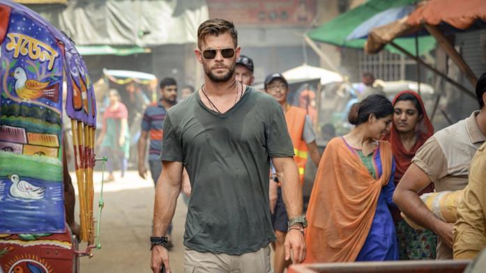Mezza figura di Chris Hemsworth che attraversa una strada in India in una scena del film