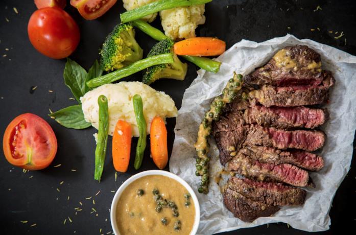 Un piatto di bistecca con verdure