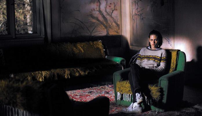 Kristen Stewart seduta nella penombra della casa infestata in una scena di Personal Shopper