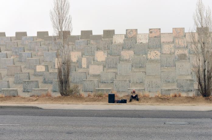 Walter White seduto alla base di un muro di Albuquerque