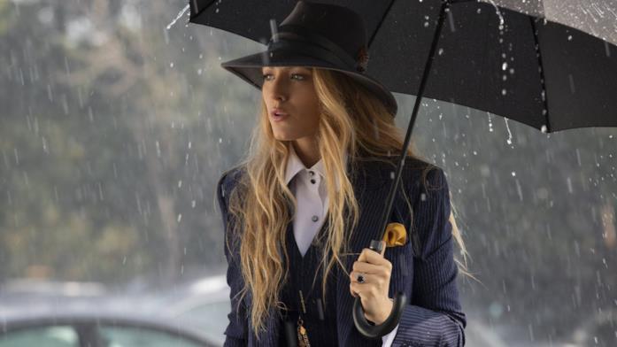 Emily, vestita con un elegante completo maschile, sotto la pioggia