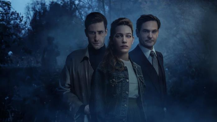 Tre persone stanno camminando in una foresta immersa nelle tenebre