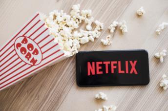 Il logo di Netflix sul display di uno smartphone, a sinistra dei pop corn