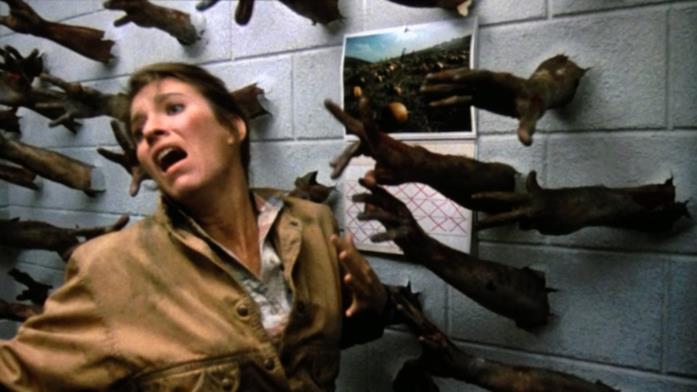 Una scena di Day Of The Dead, in cui degli zombi cercano di afferrare la protagonista