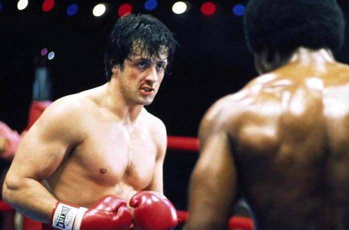 Un'immagine che vede Sylvester Stallone nei panni di Rocky Balboa mentre bonxa con Apollo Creed in Rocky