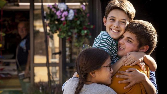 Tre bambini che si abbracciano