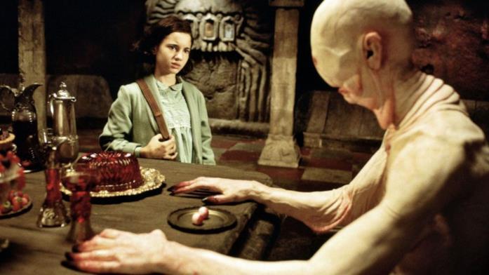 L'Uomo Pallido siede alla tavola, con i propri occhi sopra un piattino, mentre Ofelia lo guarda allibita