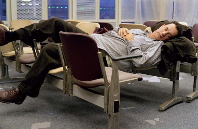 Viktor tenta di dormire sulle panchine dell'aeroporto JFK