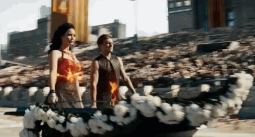 Peeta e Katniss sul carro mentre i vestiti bruciano