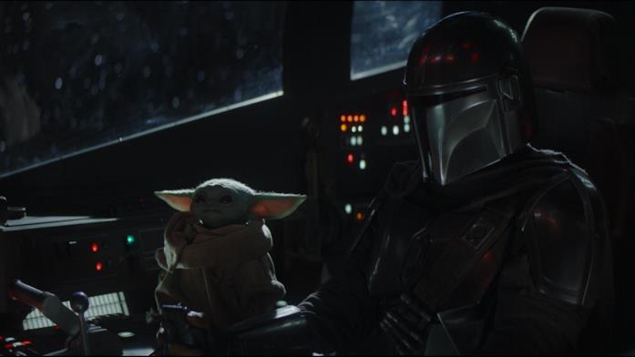 Baby Yoda e il mandaloriano Dynn Jarren in una scena della serie The Mandalorian