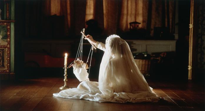 Una bambina coperta da un velo bianco gioca con una marionetta al lume di candela