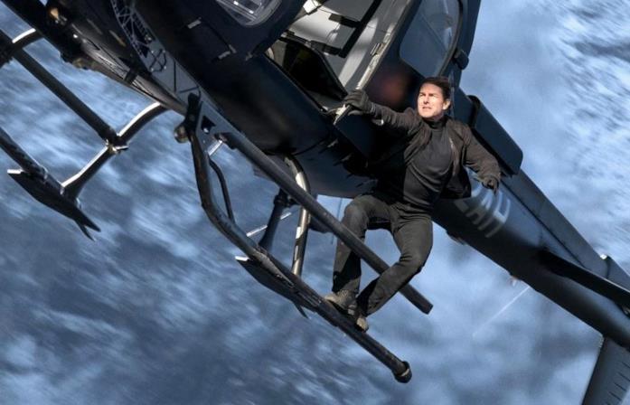 Tom Cruise aggrappato ad un elicottero in una foto del film