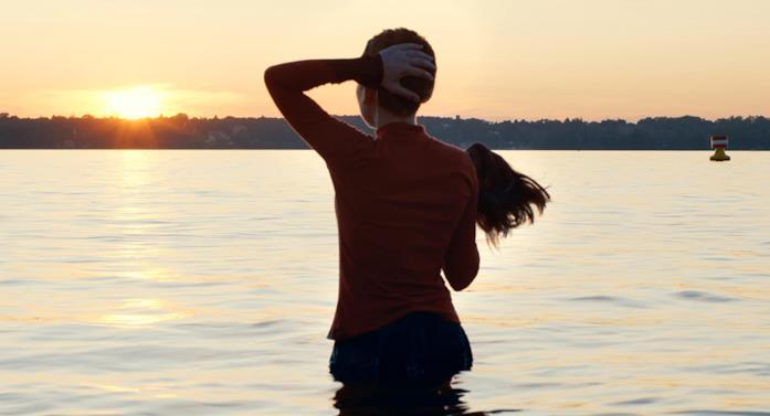 Esty (Shira Haas) si toglie lo sheitel mentre si immerge nel lago a Berlino