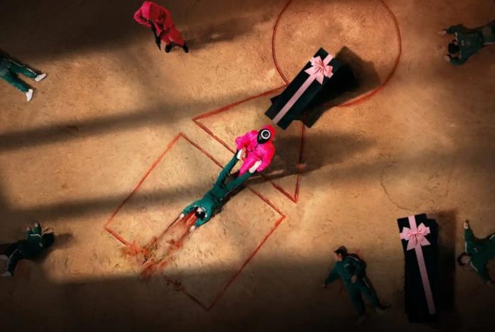 Un operatore di Squid Game porta via un cadavere