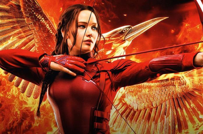 Katniss impugna arco e frecce su sfondo rosso