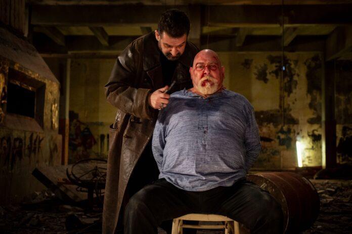 Un uomo legato a una sedia, minacciato dal suo aguzzino