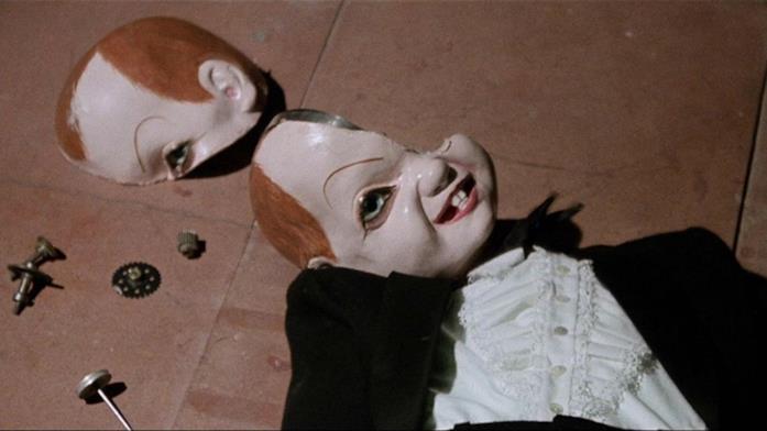 Una bambola dal ghigno malefico e il cranio spaccato
