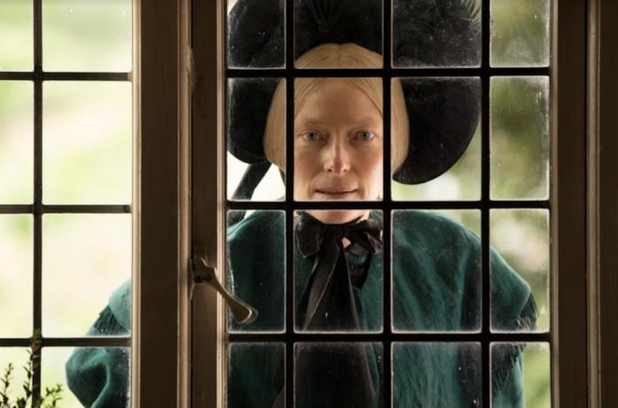 Tilda Swinton spia da una finestra