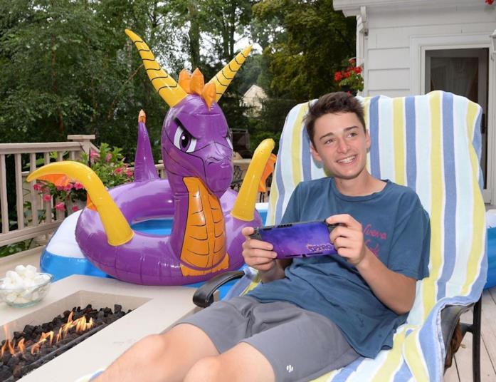 Noah Schnapp nel 2019 mentre gioca ai videogame su una sdraio
