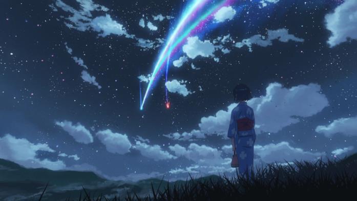 Una cometa illumina un cielo pieno di stelle, mentre una ragazza guarda la scena