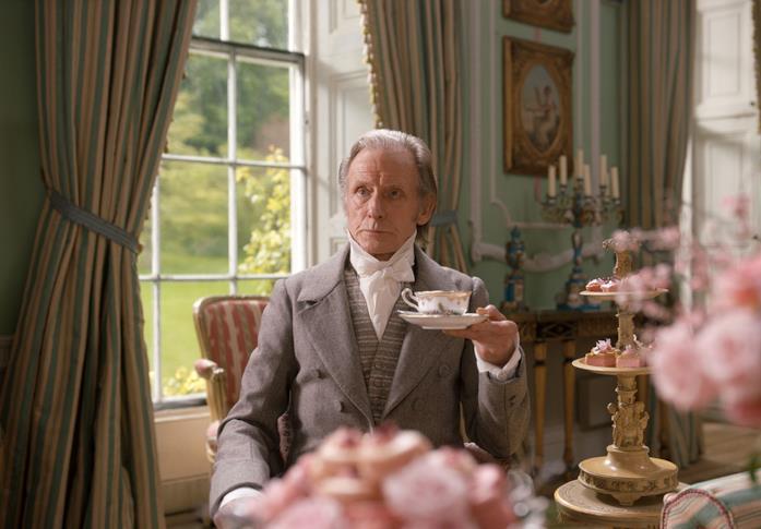 Il padre di Emma regge una tazza e piattino da tè con espressione sconcertata