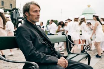 Mads Mikkelsen seduto su una panchina