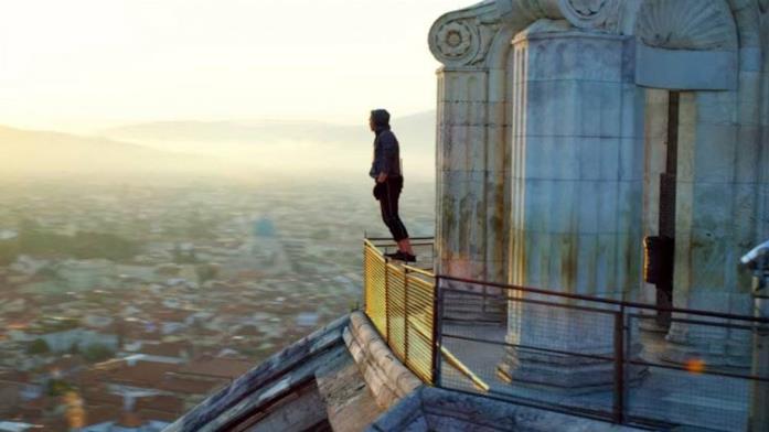 Un membro dei 6 Underground in equilibrio precario sulla ringhiera in cima al Duomo di Firenze