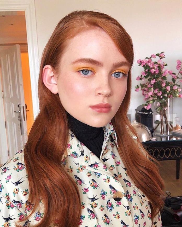Primo piano di Sadie Sink, con vestito a fiori e trucco ambra