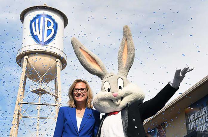 Il CEO di Warner Bros. Ann Sarnoff e Bugs Bunny; alle spalle il nuovo logo aziendale