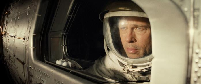 Brad Pitt guarda fuori al finestrino della sua navicella in una scena del film