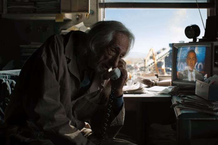Il Vecchio Joe parla al telefono nella sua discarica, con una TV sullo sfondo