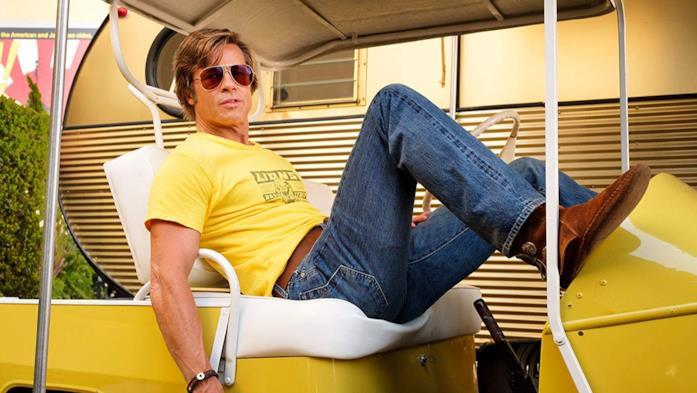 Brad Pitt in jeans e T-Shirt su una golf cart gialla in una scena del film