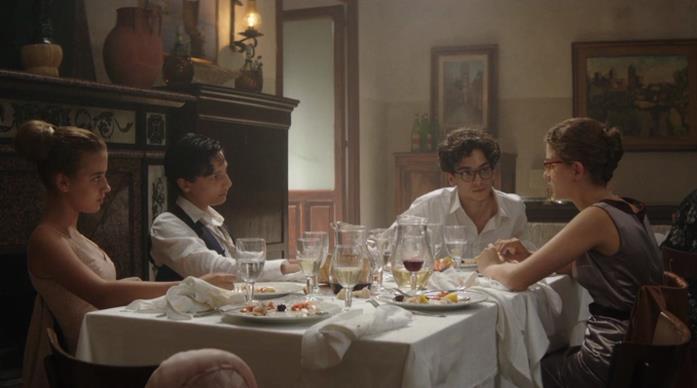 Lenù al tavolo con Alfonso e Nino al matrimonio di Lila