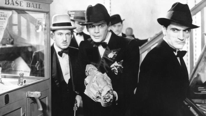 Tony Camonte (Paul Muny) nasconde una pistola in una busta di carta, circondato dai suoi scagnozzi