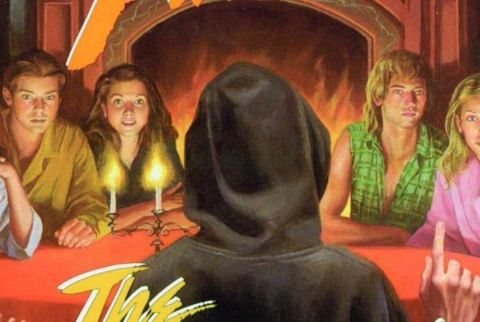 Un gruppo di ragazzi è seduto attorno a un tavolo con la coperta rossa e le candele accese
