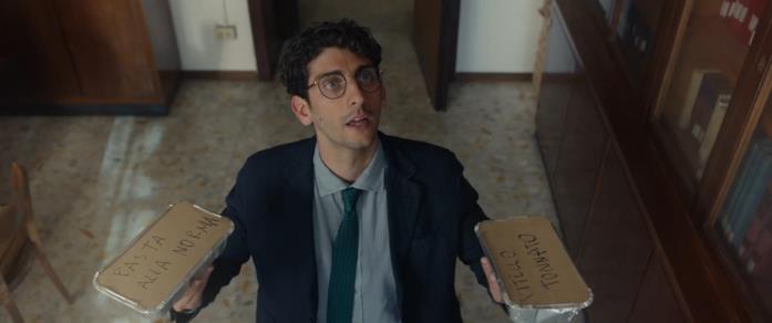 Federico (Pietro Castellitto) ha in mano due porzioni di pasta, mentre parla con un uomo