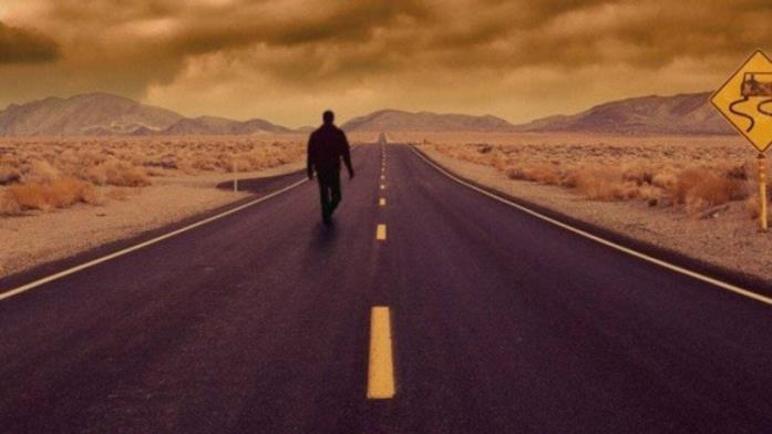 Un uomo cammina solo in una strada deserta in un'immagine promozionale de L'ombra dello scorpione (1994)
