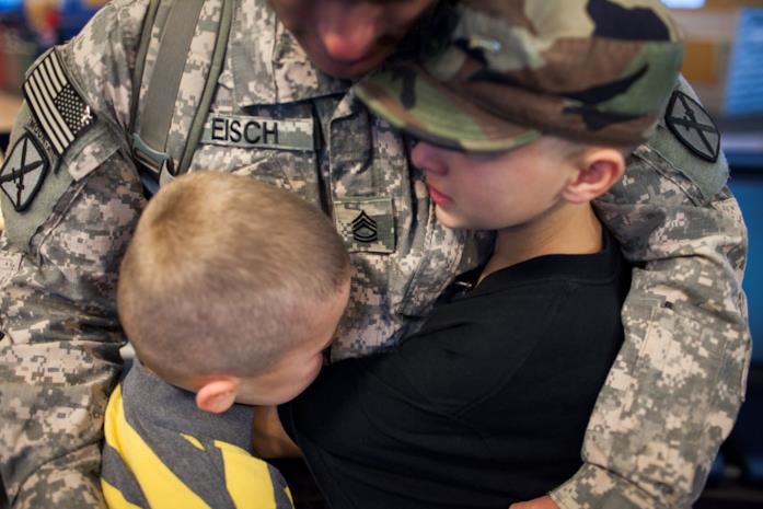 Il sergente abbraccia i suoi due figli