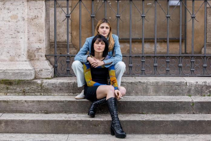 Chiara e Ludovica si abbracciano mentre sono sedute su degli scalini