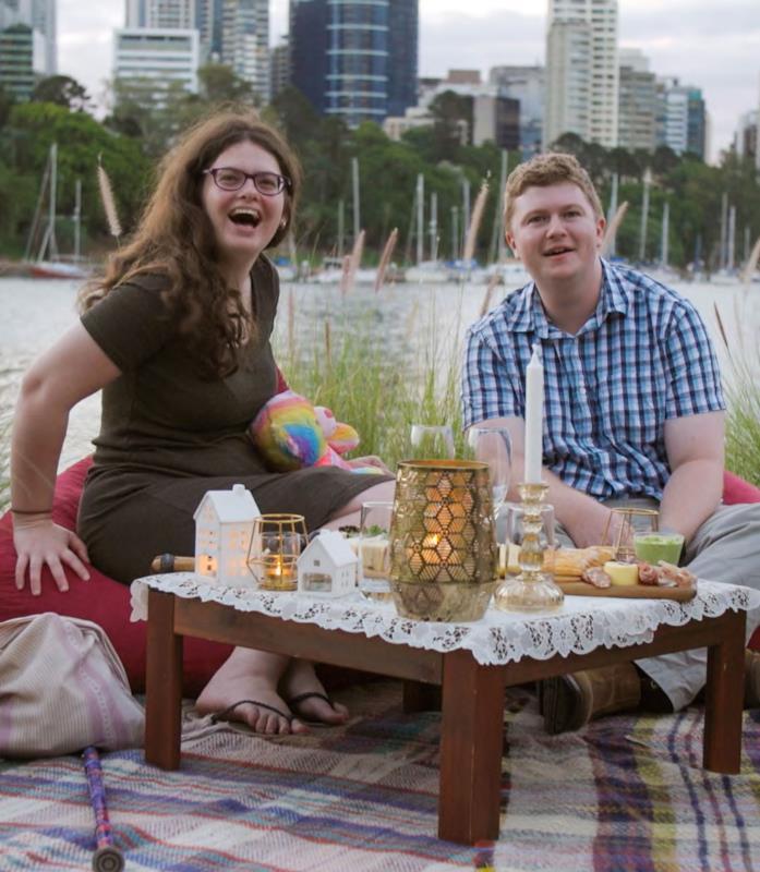 Ruth e Thomas seduti a un tavolino basso pieno di candele