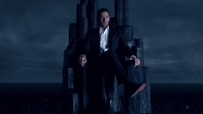 Tom Ellis seduto sul suo trono in una scena della serie TV Lucifer