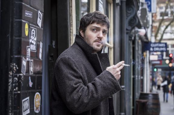 Tom Burke fuma in una scena della serie TV Strike