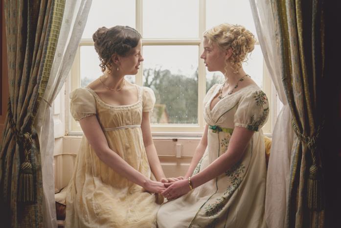 Mia Goth e Anya Taylor-Joy nei panni di Harriet e Emma si stringono le mani