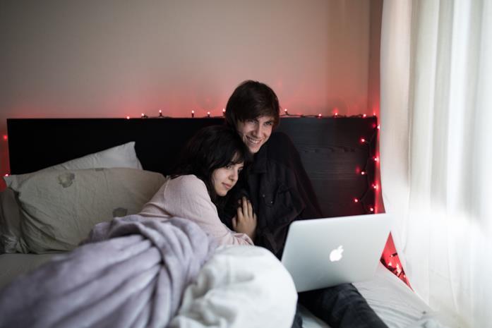 Una coppia mentre guarda un film a letto