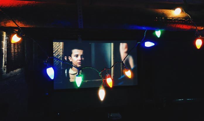 Schermo con la serie tv Stranger Things e luci colorate