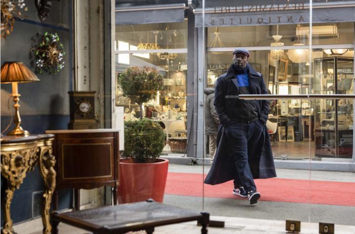 Omar Sy è Arsene Lupen mentre cammina davanti a un negozio