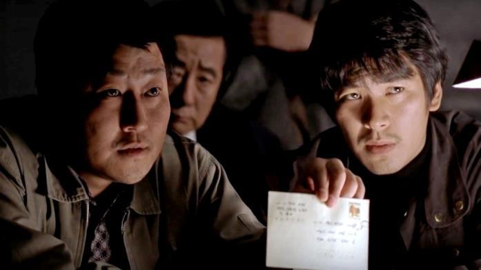 I detective protagoinisti di Memorie di un assassino mostrano una lettera