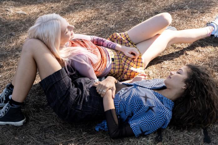 Zendaya e Hunter Schafer stradiate a terra, mentre ridono complici