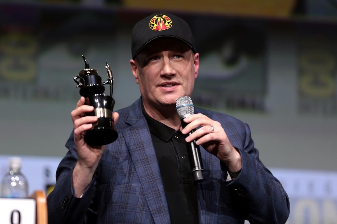 Kevin Feige con un premio in mano e un microfono, mentre parla