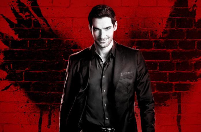 Lucifer Morningstar, con alle spalle un muro rosso, sorride